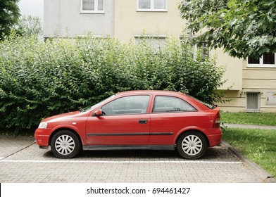 Red Opel Astra car parked on a parking spot next to a green bush on July 2017 in Poznan, Poland