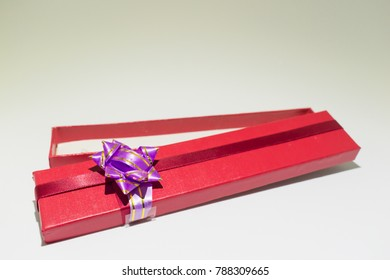 Red open gift box isolated with purple blow on white background