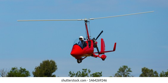Red open-cockpit autogyro flying in clear blue sky