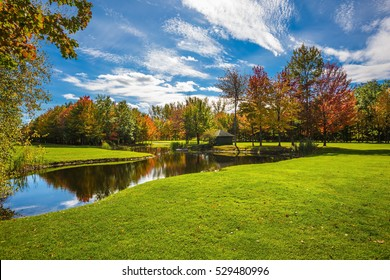 Red and orange autumn foliage reflected in the clear water of the lake. Concept of recreational tourism. Park fantastic beauty. Shining sunny day in French Canada