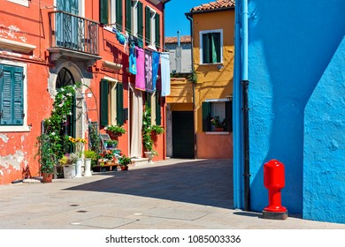 Red, orange and blue houses along narrow street in famous town of Burano, Italy.