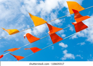 red and orange bunting flags against a blue sky