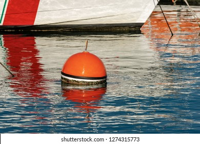 Red and orange buoy for mooring boats on the surface of the water in the port. Mediterranean sea, Italy