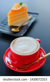 Red cup​ cappuccino​ coffee​ and​ orange cake background