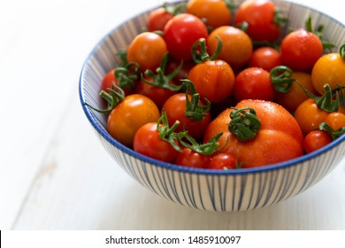 Red and Orange Cherry Tomatoes in Blue Bowl
