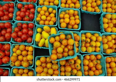 Red and orange cherry tomatoes displayed in green container pattern