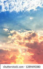 red and orange color light in fluffy clouds with sun rays in blue sky