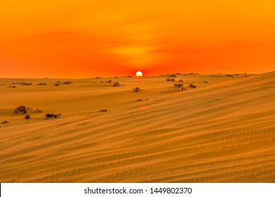 Red and orange colors of sunset sky over sand dunes at Inland Sea. Desert landscape near Qatar and Saudi Arabia. Khor Al Udeid, Persian Gulf, Middle East. Discovery and adventure travel concept.