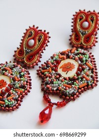 Red and orange earrings on white background