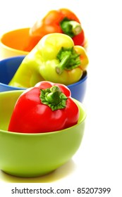 Red, orange and green peppers in color plates on a white background.