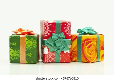 Red, orange and green present boxes isolated on white background and closed. One rectangular in the center and two square on the sides