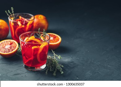 Red orange juice in a large glass or blood orange sparkling vodka cocktail or aperitif with campari on dark concrete background, copy spice, shallow depth of the field.