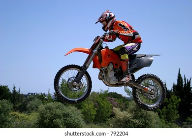 Red and orange Moto x or motor cross bike giving big air on dirt track in sunny Marbella, Spain