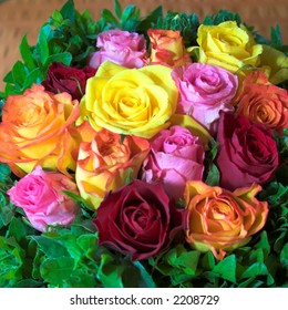 Red, orange, pink and yellow roses in a fresh arrangement at a wedding