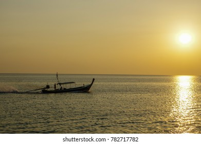 red and orange purple sunset over the sea of Thailand with a longtrail boat