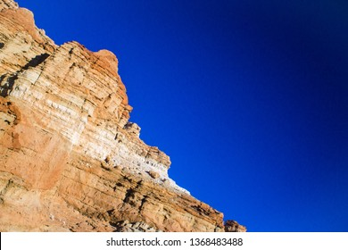 Red and orange rocks form a cliff face above the hot sands of the desert floor.