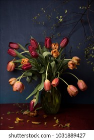 red and orange tulips in vase on red table