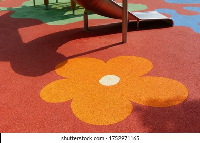 Red, orange, yellow and blue color padded rubber safety sports flooring with flower pattern in kids playground. leisure, outdoors and sports activity concept. active lifestyle. leisure and relaxation.