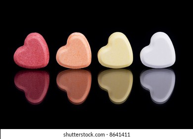 Red, orange, yellow and white candy hearts with reflection