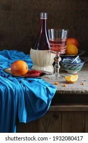 rote Orangen und Wein auf einem Holztisch