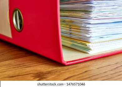 Red ordner with papers. Stack of business papers, bills or documents in ordner document binder closeup on wooden desk. Debt free life, business office stress workload or paperless office concept.