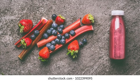 Red organic fruits and berries smoothie with rhubarb, blueberries and strawberries in bottle on gray granite table , top view. Healthy dieting and antioxidant beverage