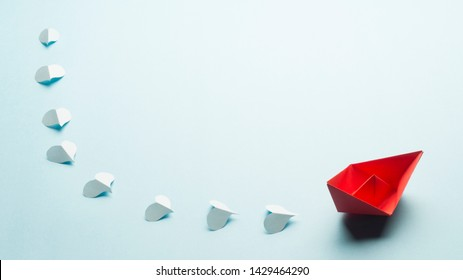 Red origami boat and blue paper hearts in a line behind the boat