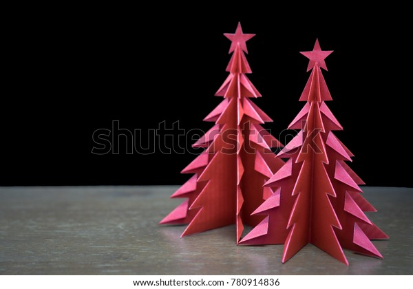 Red Origami Christmas Trees on a wooden table with black wooden background.