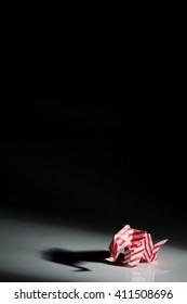 Red origami elephant isolated on black background