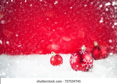 Red Ornaments on Snow With Blurred Red Lights In Background