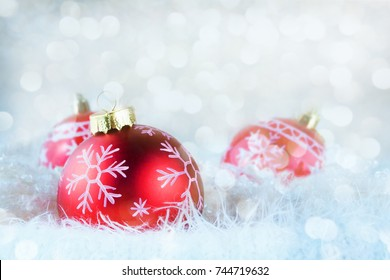 Red Ornaments on Snow With Blurred White Lights In Background. Christmas Card - Baubles On Snow