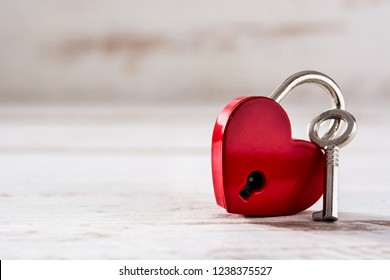 Red padlock hearts with key on white wooden background. Copyspace