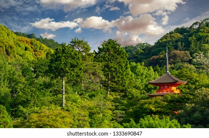 red pagoda on a green hill surrounded by trees in Kyoto, Japan