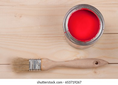 red paint in the bank to repair and brush on the light wooden background with copy space for your text. Top view