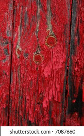 Red paint peeling on knotted wood boards