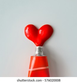 Red paint in shape of a heart on white paper background. Flat lay. Love concept.