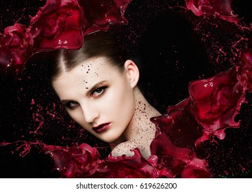 Red paint splash over beauty makeup  fashion model girl abstract on black background