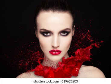 Red paint splash over beauty makeup fashion model girl with black smokey eyes abstract on black background