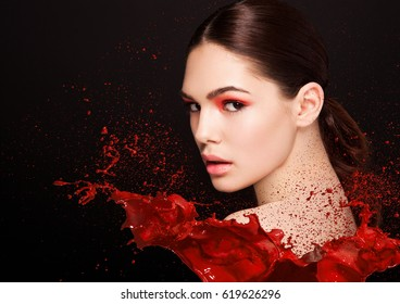 Red paint splash over beauty makeup fashion model girl with red smokey eyes abstract on black background