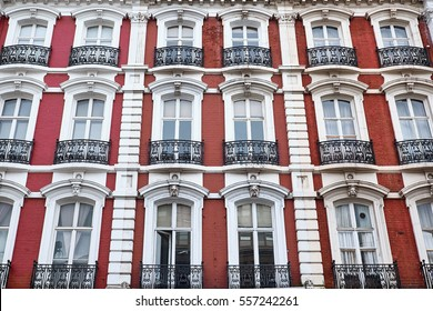 Red painted brick facade with white decorations around arched windows and balconies of a british apartment building in London City