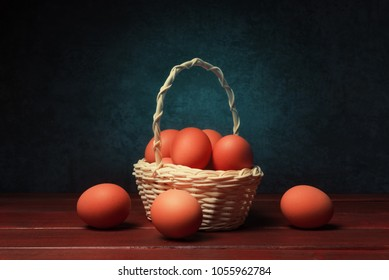 Red painted eggs in basket against dark blue stone background.