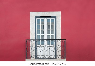 red painted house facade with small iron balcony and white lattice door, white and grey framed. space for text