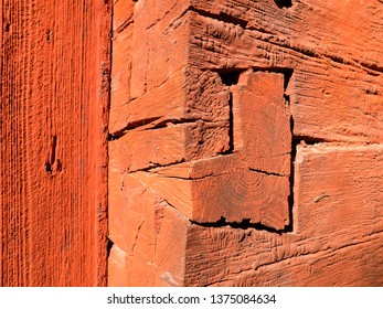 Red painted log cabin corner notches