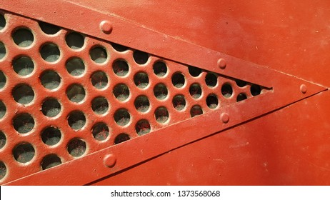 Red painted metal surface with triangle shape dotted lattice window. Round hole pattern metal grid closeup. Abstract background. Vintage industrial backdrop. Red riveted frame of triangle window.