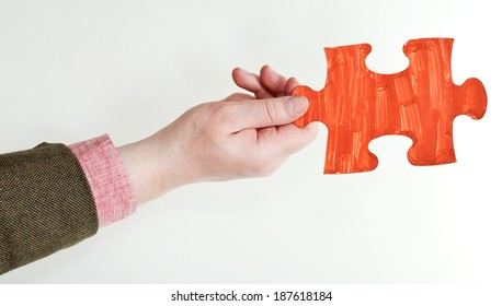 red painted puzzle piece in male hand on grey background
