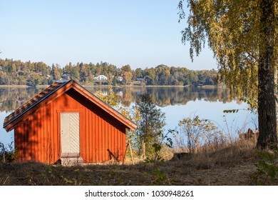 A red painted small hut by a lake on a sunny fall day.