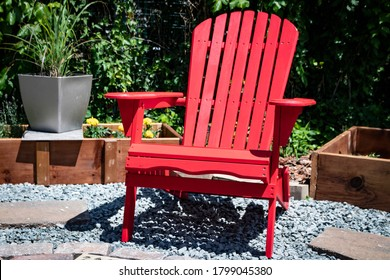 Red painted wooden Adirondack chair sits in sunshine filled backyard garden courtyard.