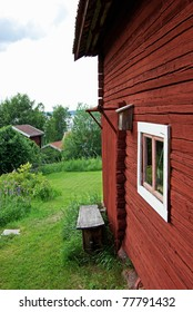 Red painted wooden cottage in a Swedish rural landscape.