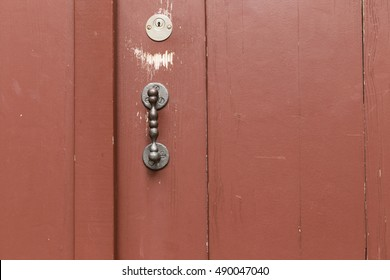 A red painted wooden door with vertical planks, metal door handle and key hole.