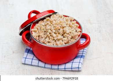 Red pan with boiled wheat porridge - traditional meal in Ukraine, Belarus and Russia. Close up